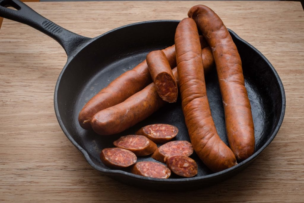 black cast iron skillet seasoned with flaxseed oil with sausages