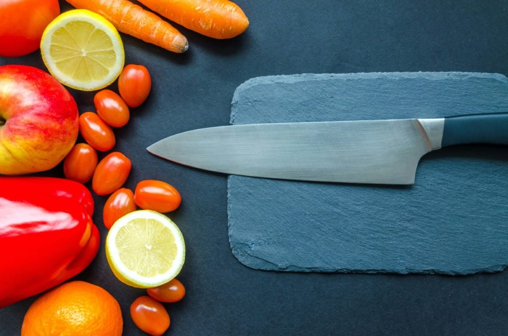 sharp Japanese knife on cutting board next to fruits and vegetables