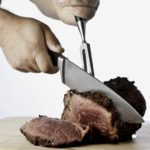 man's hands using knife and fork to cut prime rib