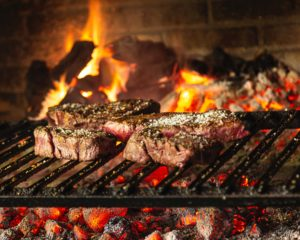 steaks on grill over hot charcoal