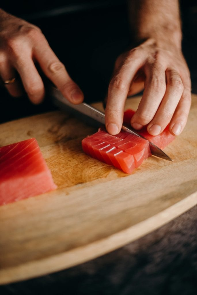 hands with knife cutting salmon on cutting board