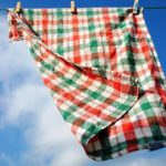 white red and green checked kitchen towel hanging on clothes line with blue sky over it