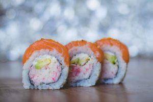 three slices of sushi roll with red roe