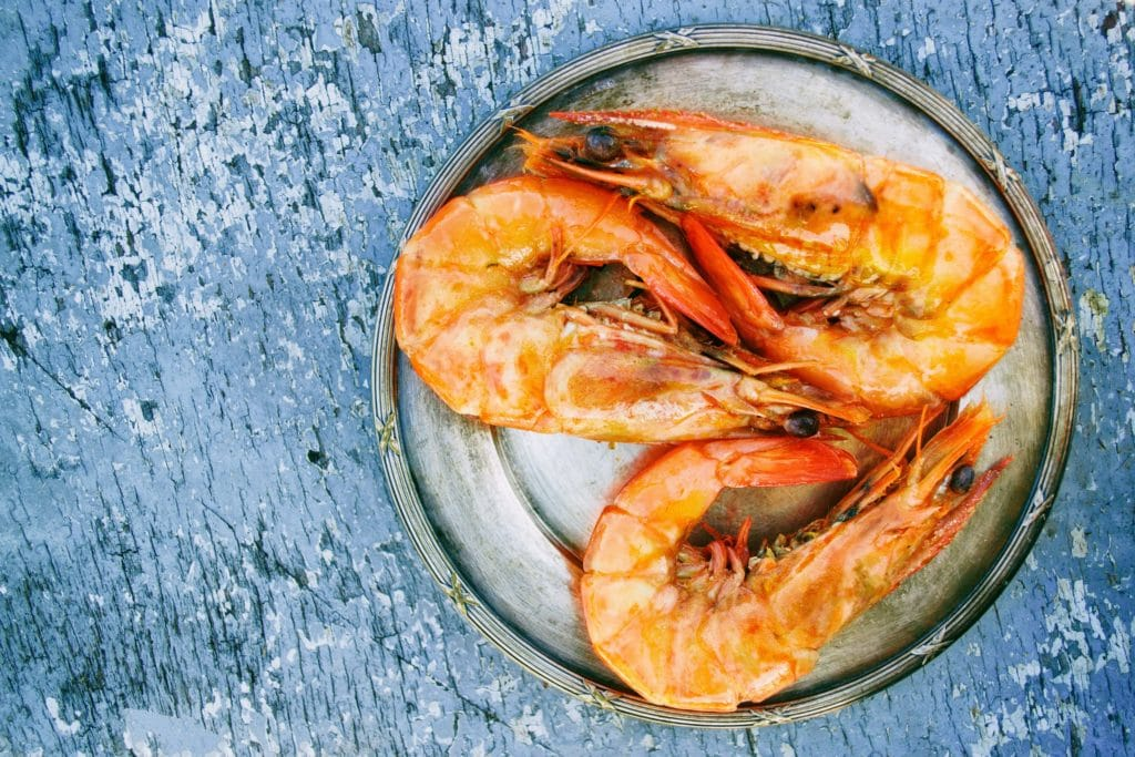 three shrimp on white plate on marble counter