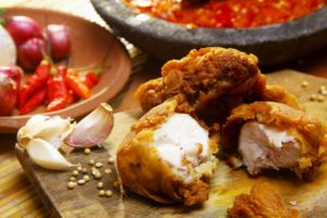 small pieces of fried chicken on wooden cutting board with herbs and spices