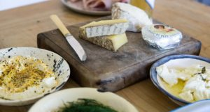 cutting board with knife and several cheeses surrounded by bowls with other appetizers