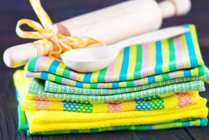stack of pastel dish towels with white spoon rest on top against black background