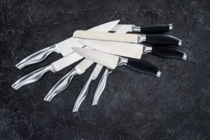 pile of eight knives on black background