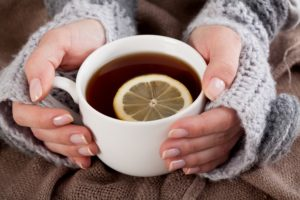woman's hands holding white mug of tea with lemon slice
