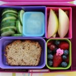 Bento box filled with lunch food - cucumbers fruit and sandwich