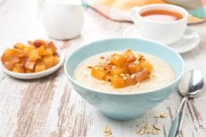 bowl of oatmeal with peaches on wooden table with glass of milk