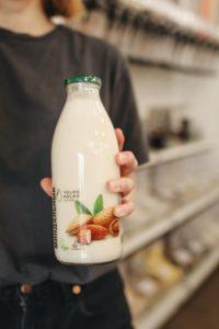 hand holding bottle of almond milk