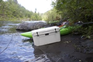 large white cooler next to green kayak on side of river