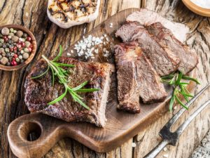 sliced brisket on cutting board surrounded by herbs and other ingredients