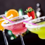 three margaritas lined up against black background