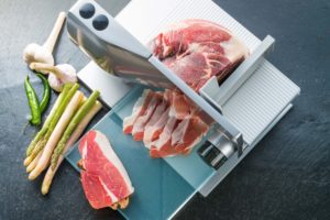 overhead view of meat slicer with meats and veggies