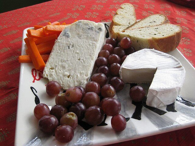 Simple addtions like grapes and carrots make the cheese board interesting and attractive.