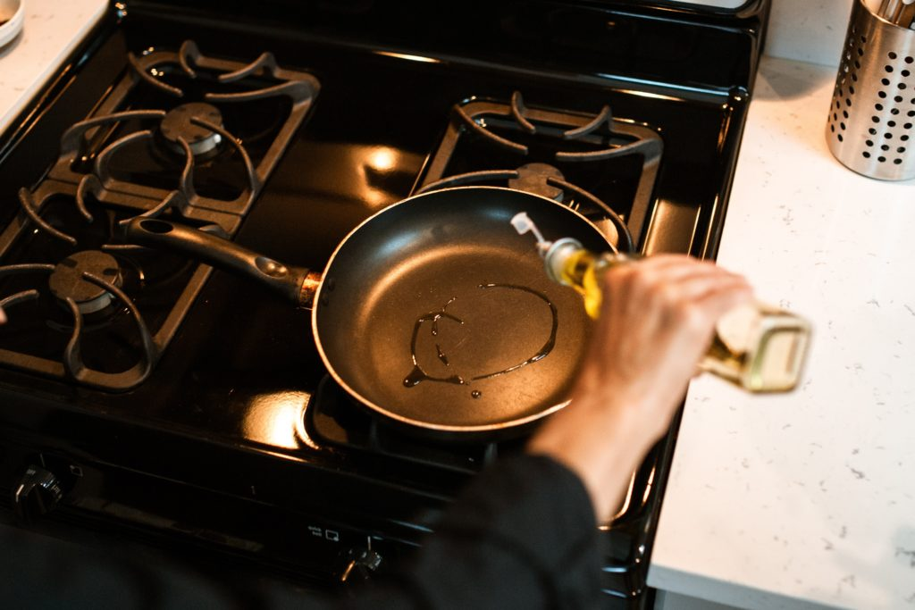 a person's hand drizzling oil from a glass jar into a black steel carbon pan on gas stovetop