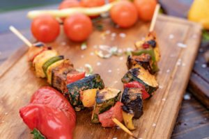 grilled kebabs on wooden cutting board with tomatoes