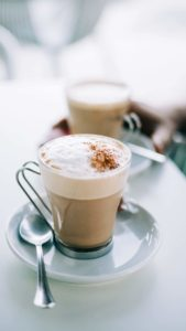 cappuccino with frothy top in glass mug on white plate with spoon