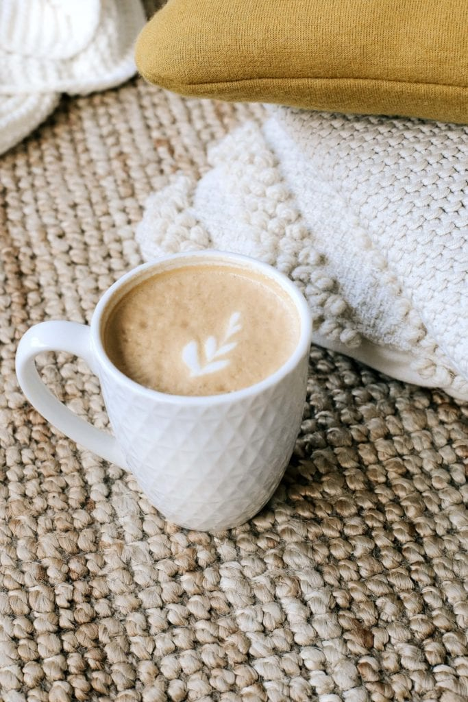 white mug of coffee with delicate milk design on top on tan tablecloth