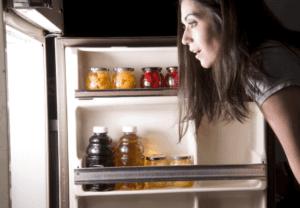 Woman Looking In An Organized Fridge