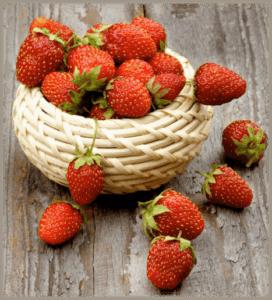 A small basket full of fresh strawberries