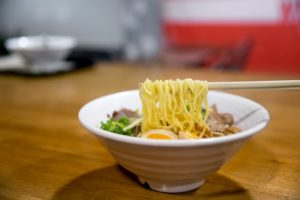 white bowl of ramen and vegetables and boiled egg on table