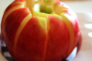 Red apple cored and sliced evenly by apple corer and apple slicer, spread slightly open from the core