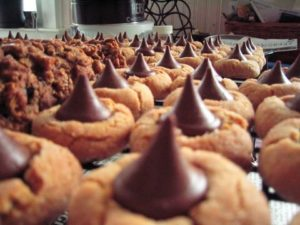 foreshortened lines of peanut butter cookies with chocolate kisses on top spreading into the distance