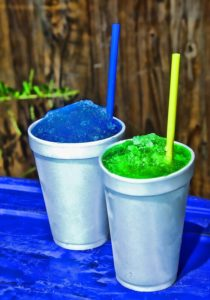 a bright blue and a bright green slushee with blue and yellow straws in white styrofoam cups on a table covered with a blue tablecloth in front of a wooden fence