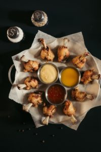 wings in circle on plate with dips in middle and salt and pepper shakers on side on black table