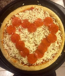 high quality pepperoni in the shape of a heart on an uncooked pizza surrounded by shredded mozzarella cheese