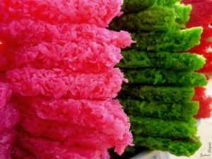 three stacks of homemade coconut candy made using candy thermometer, one bright pink, one dark green, and one red