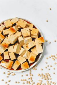 a white bowl of cubed grilled tofu with small beans scattered around it