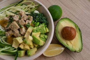 healthy salad with tofu on top in white bowl with half an avocado and lemon slice beside bowl