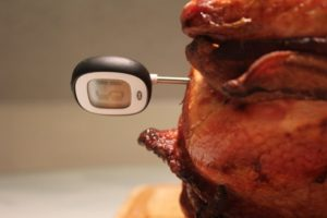 black and gray digital thermometer stuck in side of cooked turkey