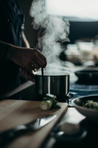 person's hand using utensil to stir steaming food in cuisinart multiclad pro pot on stove