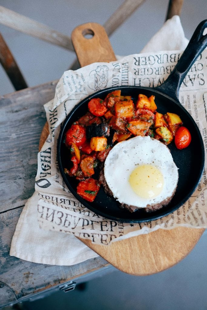 cast iron skillet with an egg and fried potatoes