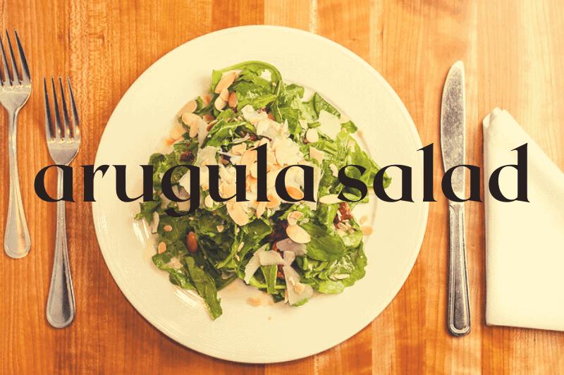 white bowl on wood table with arugula salad