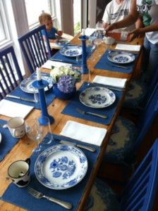 blue and white china on wood table set with blue candles and blue chairs