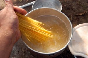 putting spaghetti in a pot with boiling water for cooking