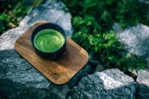 black cup of green tea on wooden cutting board on rock with greenery