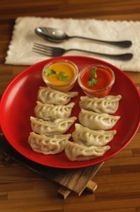 eight dumplings with two sauces on red plate on table next to white napkin with fork and spoon
