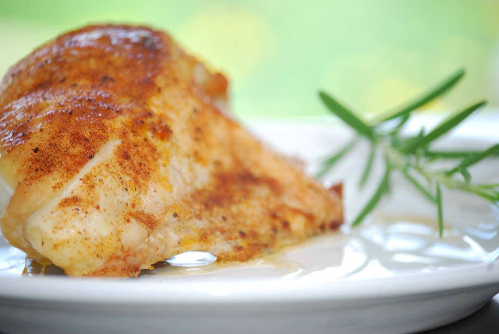 cooked chicken breast on white plate with rosemary sprig