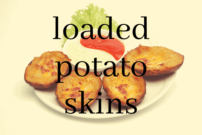 loaded potato skins on plate with dip
