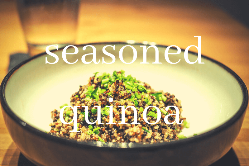 seasoned quinoa in white and brown bowl on wooden table