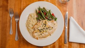 white plate on wooden table with chicken piccata and green beans