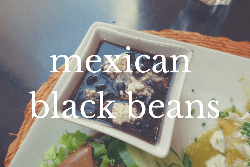 bowl of black beans in square white bowl on white plate with other food on side