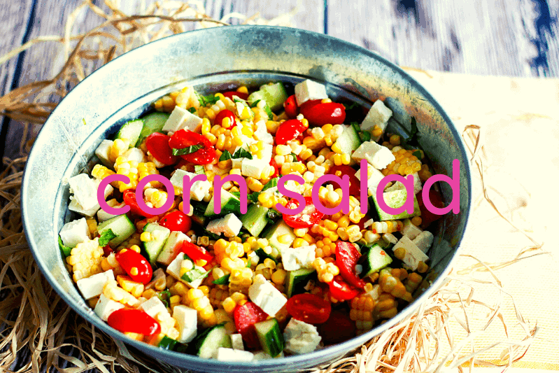 white bowl of corn salad on wood table